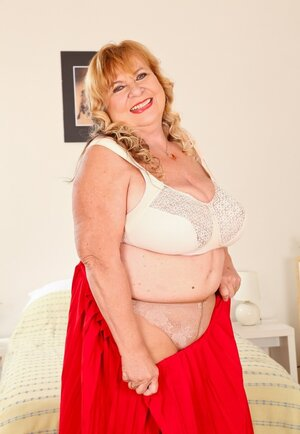 Aged BBW squeezes heavy breasts in a bra after shades long red skirt