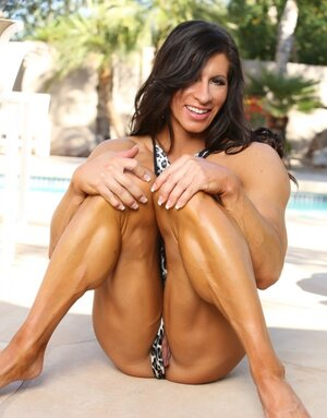Black-haired dame bodybuilder seductively unclothes by poolside