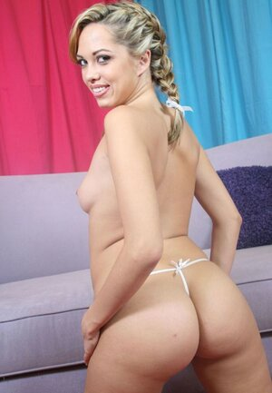 Seducing blonde smiles with enjoyment while showing her assets on camera